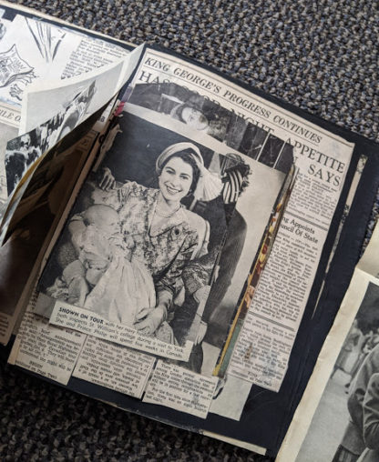 photo of Queen Elizabeth holding one of her children inside a Vintage Souvenir Book Full of early article pictures of Queen Elizabeth