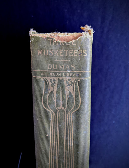 upper spine view of a 1900 copy of The Three Musketeers by Alexandre Dumas - Published by Caldwell Company Publishers